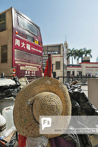 China  Hong Kong  straw hat of a street merchant in downtown Kowloon and a bus