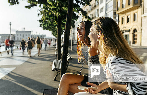 Happy friends smiling while sitting at promenade during sunset