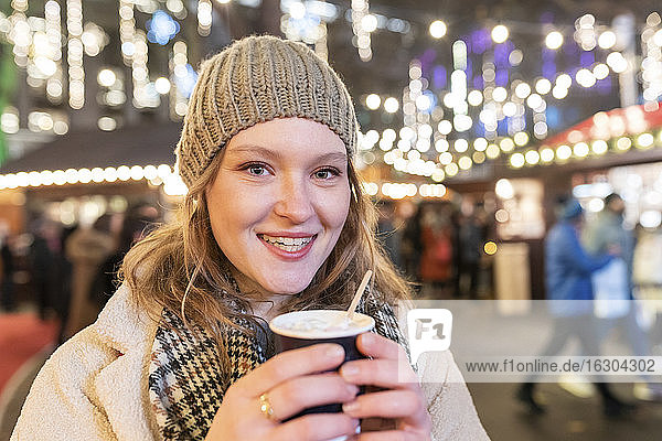 Close-up of happy beautiful woman holding hot chocolate in Christmas market at night
