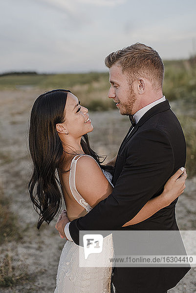 Smiling bridegroom looking at each other in field