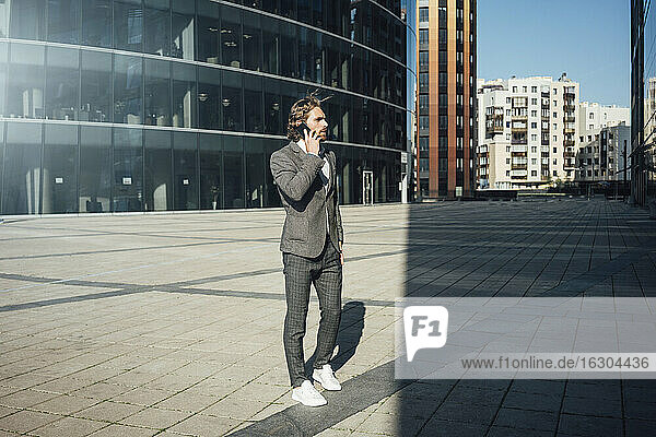 Male entrepreneur talking on smart phone while looking away at financial district during sunny day