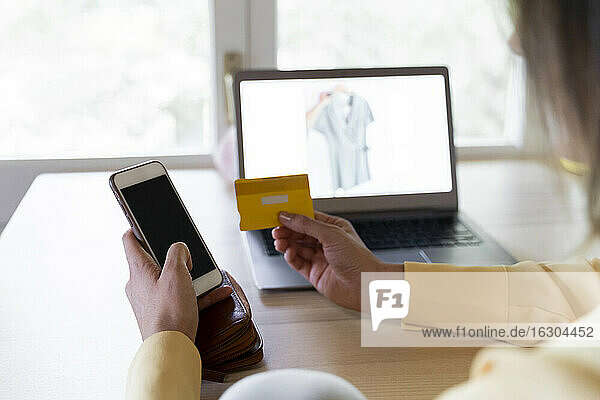 Young woman using credit card and smart phone for online shopping at home