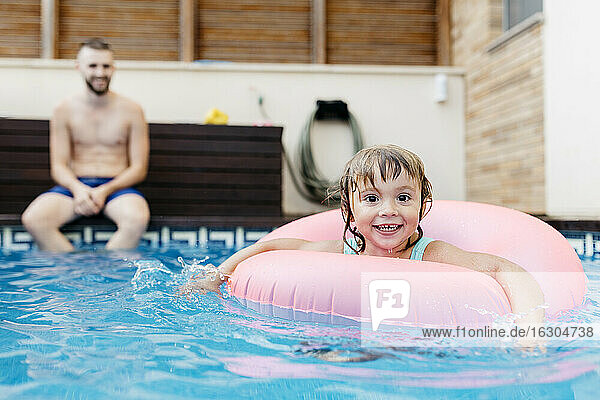 Little girl with floating tire and her uncle in swimming pool