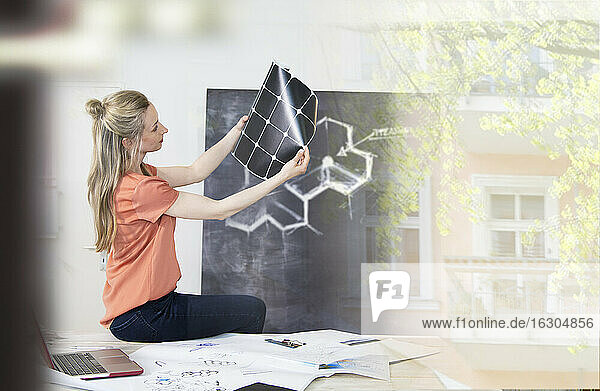 Woman sitting on desk in office looking at printout