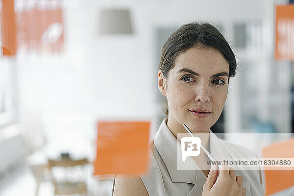 Businesswoman brainstorming while standing at office
