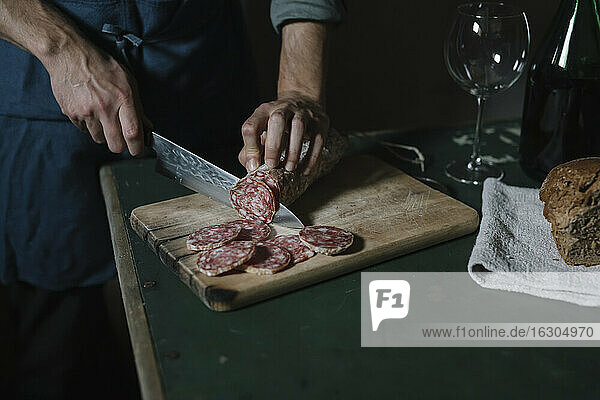 Hands of man cutting salami slices on board at table