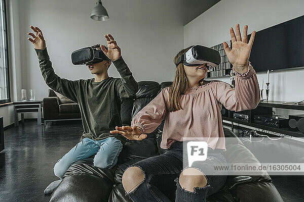 Friends looking through virtual reality simulators while relaxing on couch at home