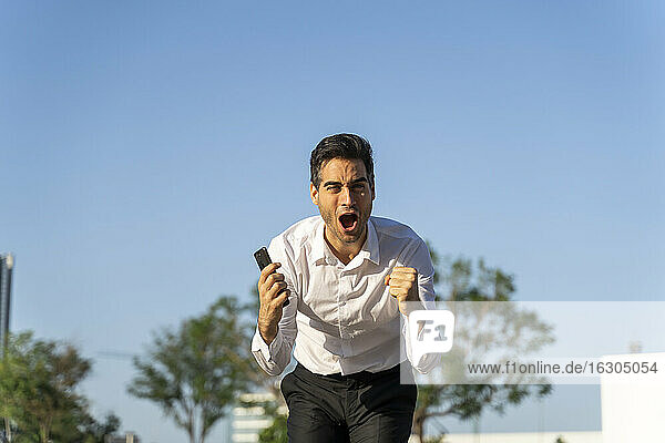 Excited businessman holding smart phone screaming while standing against clear blue sky