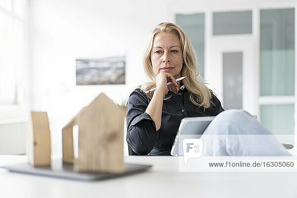 Thoughtful businesswoman with digital tablet looking at model on desk while sitting in home office