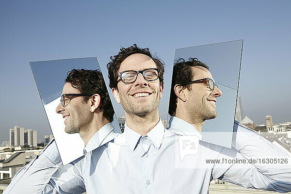 Portrait of smiling man holding two mirrors