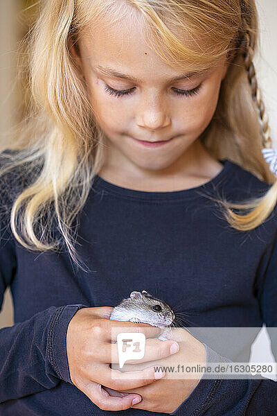 Cute little girl playing with hamster