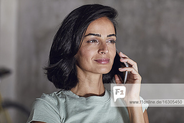 Close-up of confident businesswoman talking over smart phone in office