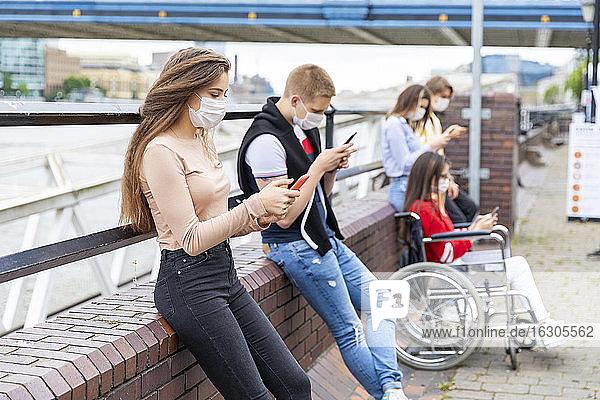 Junge Freunde halten bei der Benutzung von Handys in der Stadt einen Sicherheitsabstand ein