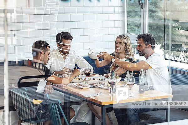Freunde genießen eine Mahlzeit im Restaurant durch ein Fenster gesehen