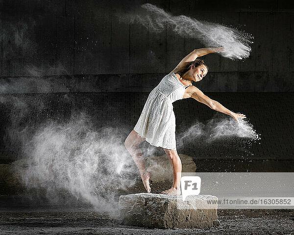 Beautiful woman dancing while splashing flour against wall