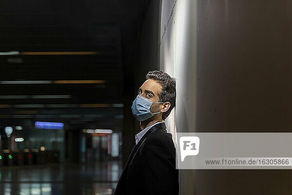 Male entrepreneur wearing mask while leaning on white wall at station