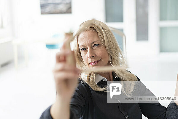 Close-up of confident businesswoman looking through model in home office