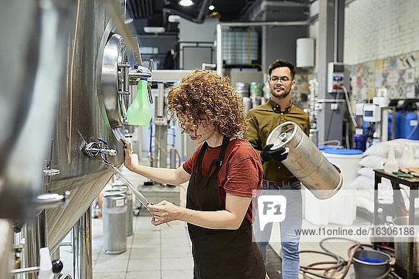 Mann und Frau arbeiten in einer Handwerksbrauerei Mann und Frau arbeiten in einer Handwerksbrauerei