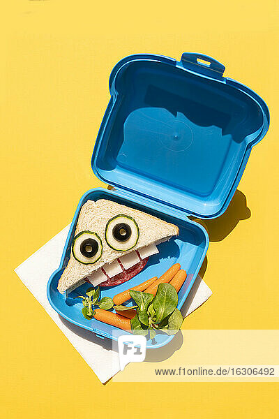 Lunch box with baby carrots and funny looking sandwich with anthropomorphic face