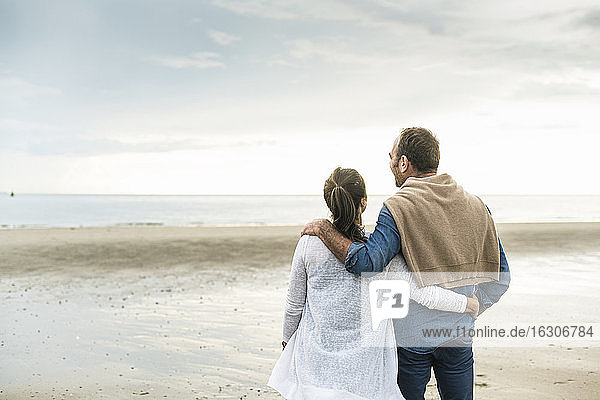 Couple with arms around looking at sea against cloudy sky during sunset