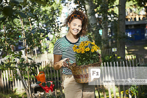 Smiling young woman holding basket with yellow flowers while standing in back yard garden