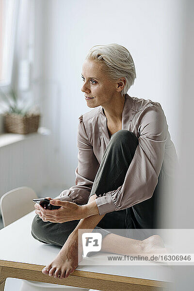 Thoughtful female professional holding mobile phone while sitting on desk in office