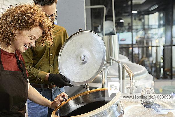 Mann und Frau arbeiten in einer Handwerksbrauerei und schauen in den Tank Mann und Frau arbeiten in einer Handwerksbrauerei und schauen in den Tank