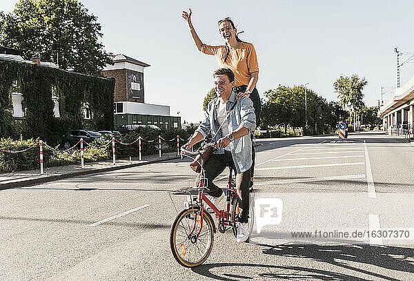 Cheerful young woman standing behind boyfriend riding bicycle on street