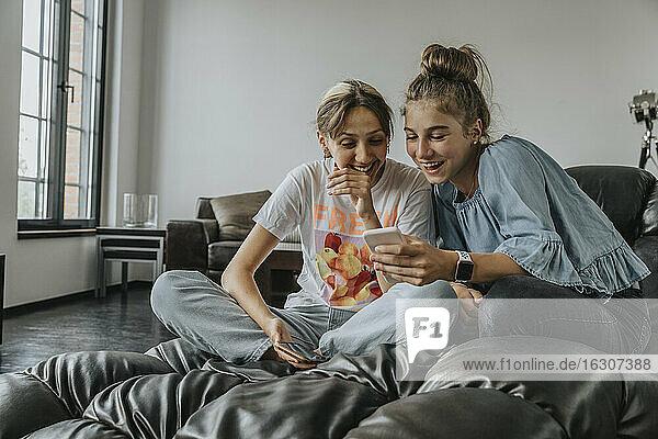 Fröhliche Freunde benutzen ein Smartphone  während sie sich zu Hause auf der Couch entspannen