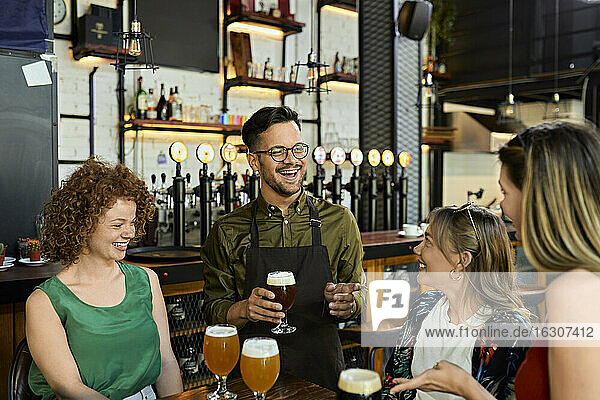 Waiter serving craft beer for female friends in a pub