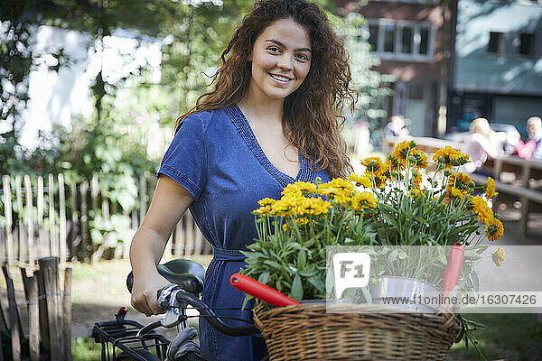 Young woman with flower pots in basket of bicycle