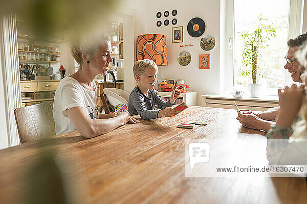 Family playing cards while sitting at dining table during weekend