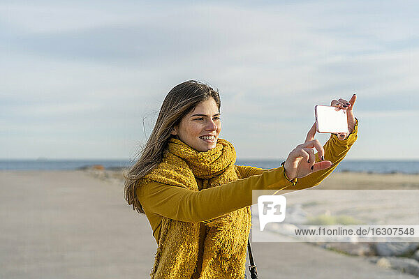 Smiling woman taking photograph through mobile phone looking away against sky