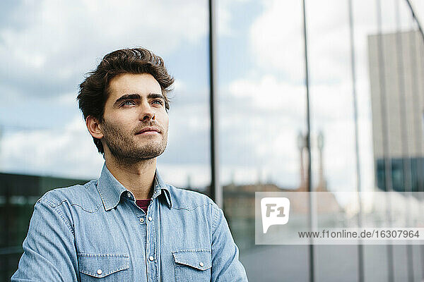 Close-up of thoughtful casual businessman looking away against modern building