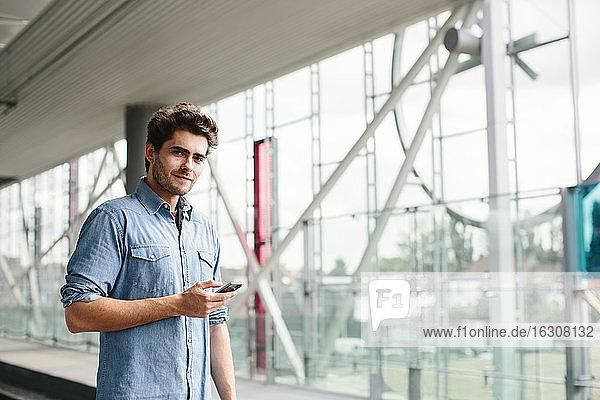 Selbstbewusster Geschäftsmann  der sein Smartphone benutzt  während er am Bahnhof steht Selbstbewusster Geschäftsmann, der sein Smartphone benutzt, während er am Bahnhof steht