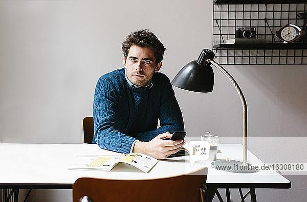 Männlicher Architekt  der ein Smartphone auf dem Schreibtisch benutzt  während er im Büro sitzt Männlicher Architekt, der ein Smartphone auf dem Schreibtisch benutzt, während er im Büro sitzt