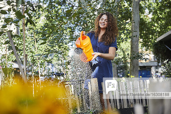 Young woman watering flowers in garden