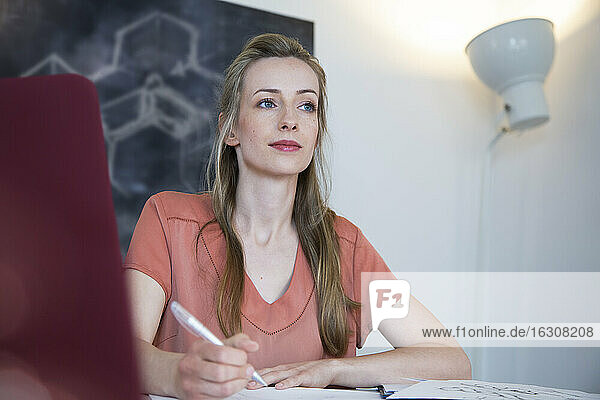 Thoughtful woman working at desk in home office