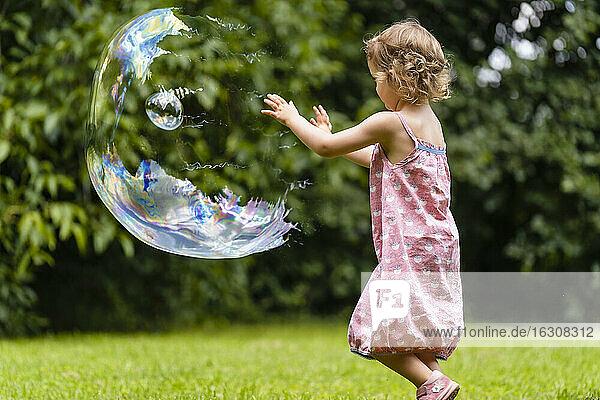 Cute girl exploding bubble at public park