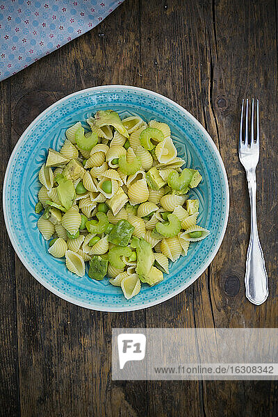 Plate of noodle salad with avocado  peas and celery on wood  elevated view