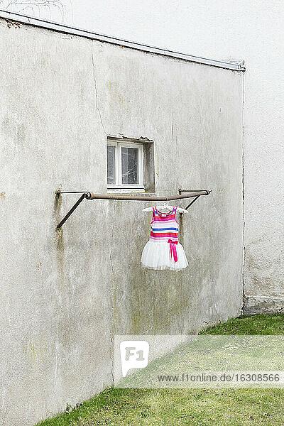 Deutschland  düsterer Hinterhof mit Kinderkleidern an der Kleiderstange