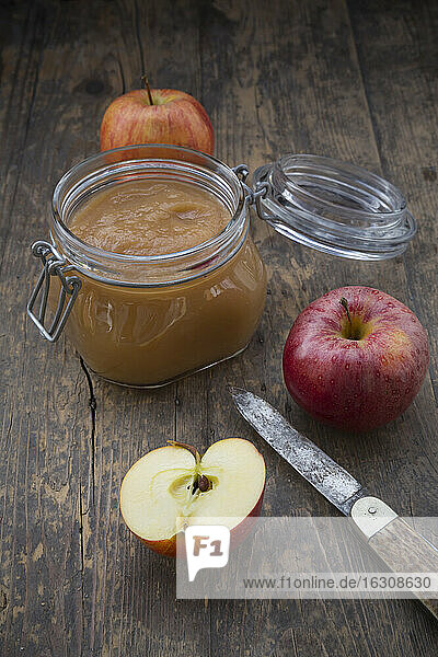 Apple puree in bottling jar and apples on wooden table