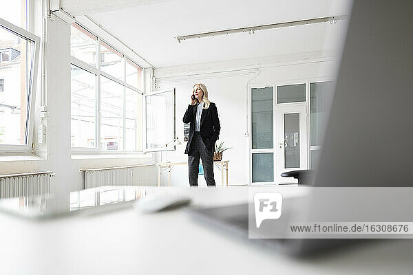 Female entrepreneur talking over smart phone while standing at home