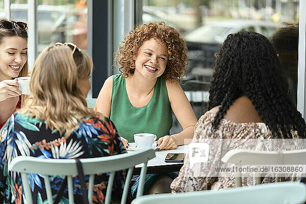 Happy female friends meeting in a cafe