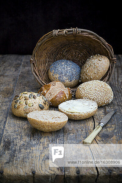 Different whole meal bread rolls  bread basket  knife and butter