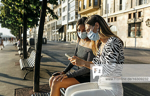 Young friends with face mask using phone while sitting on bench at promenade