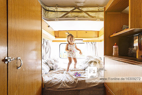 Cheerful girl jumping on bed in motor home