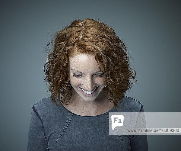 Porträt einer lächelnden rothaarigen Frau mit Blick nach unten