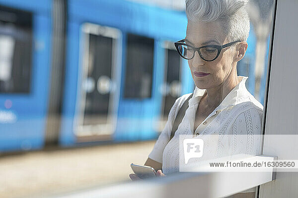 Senior woman text messaging on smart phone while standing at tram stop