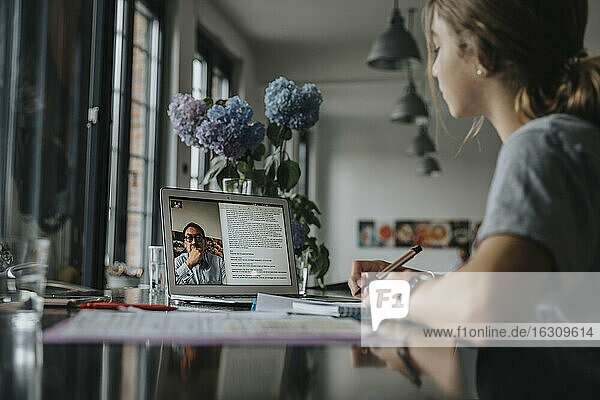 Teenage girl studying from home  using laptop